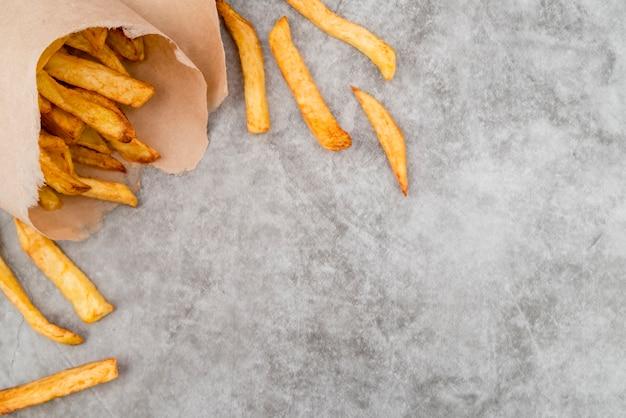 Вкусный картофель фри на сером столе