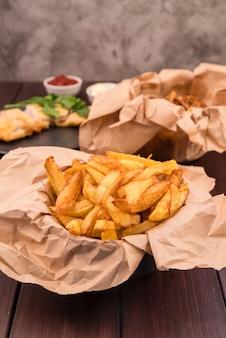 Вкусный картофель фри на деревянном столе