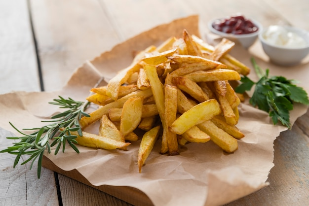 Yummy french fries on wooden table