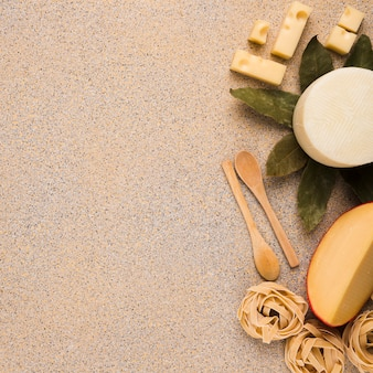 Yummy fresh types of cheeses with raw pasta ; bay leaves and wooden spoon over marble texture surface