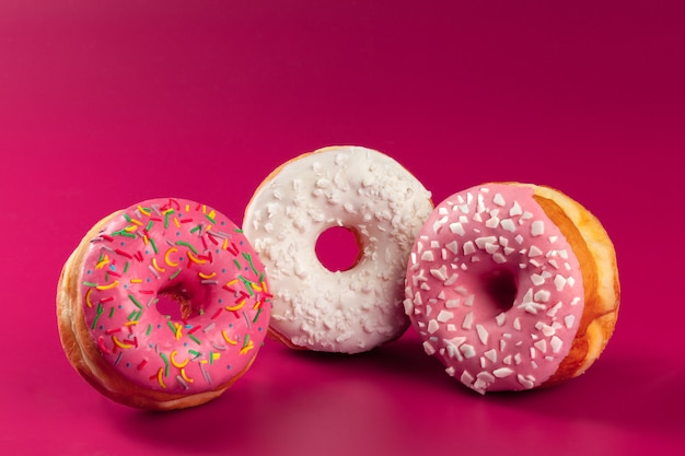 Yummy glazed round donut on a bright pink background