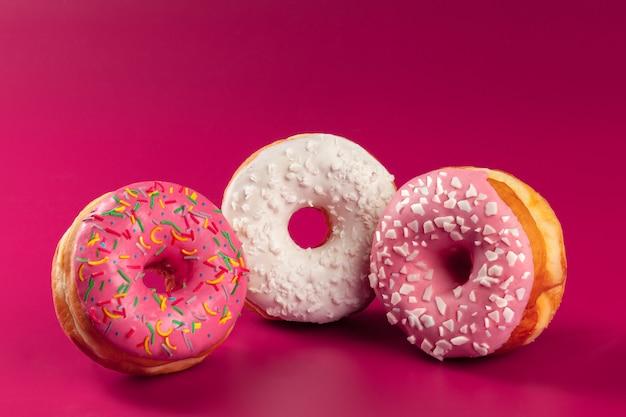 밝은 분홍색 배경에 맛있는 유약 둥근 도넛