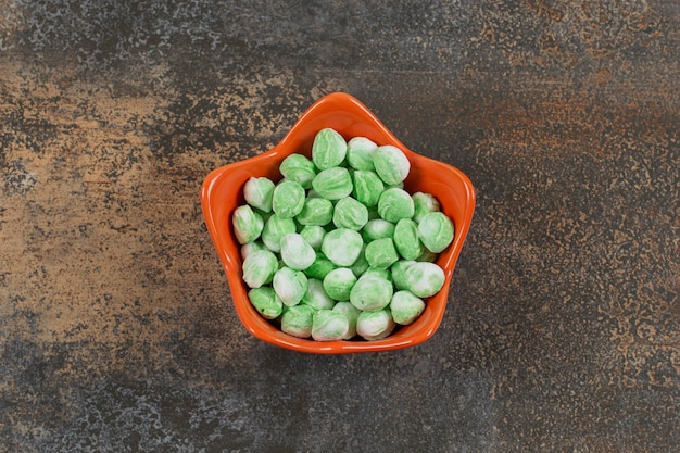 Вкусные зеленые ментоловые конфеты в оранжевой миске.