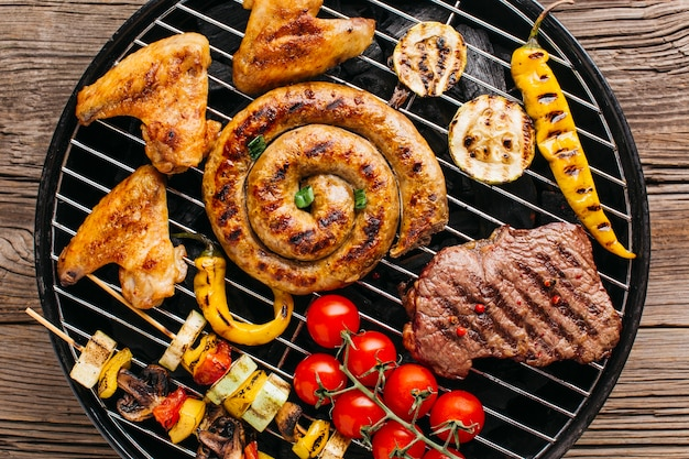 Yummy grilled spiral sausages and meat with vegetable on barbecue grill