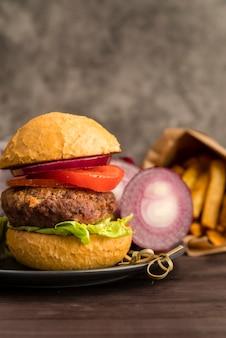 Вкусный гамбургер с луком и картофелем фри