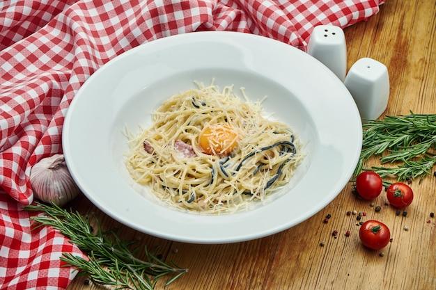 木の上の白いボウルにベーコン、卵黄、パルメザンチーズを使ったおいしい自家製パスタカルボナーラ。