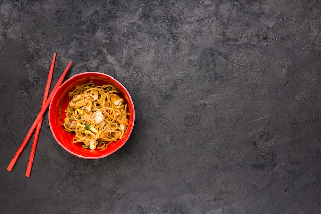 Yummy japanese chicken noodles in red bowl with chopsticks over textured black slate