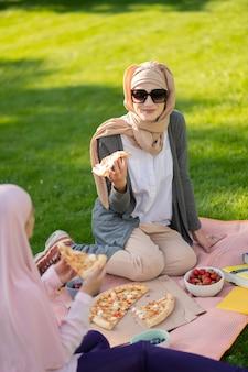 밖에서 맛있는 점심. 친구와 함께 밖에 서 맛있는 점심을 먹고 선글라스를 착용하는 이슬람 여성