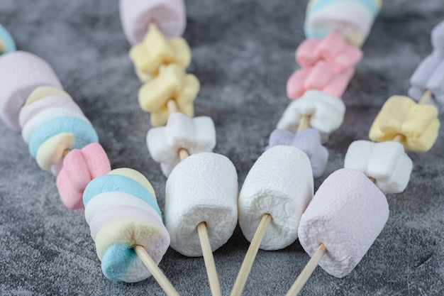 Yummy marshmallows on the wooden sticks to be grilled.