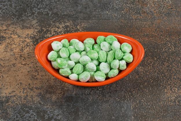 Вкусные ментоловые конфеты в оранжевой миске.