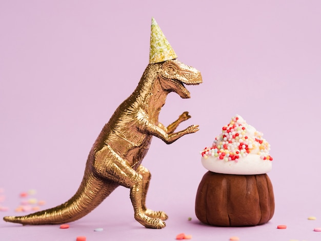 Yummy muffin and dinosaur with birthday hat