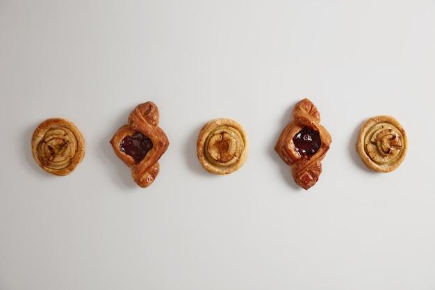 Deliziosi pasticcini o biscotti ripieni di marmellata, dolciumi appena sfornati. panini domestici da forno. torte per il tè a colazione. prodotti ipercalorici, gastronomia, prodotti da forno e concetto di dolce tentazione