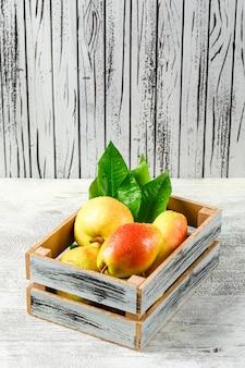 Pere squisite con le foglie in una scatola di legno su fondo di legno e grungy bianco