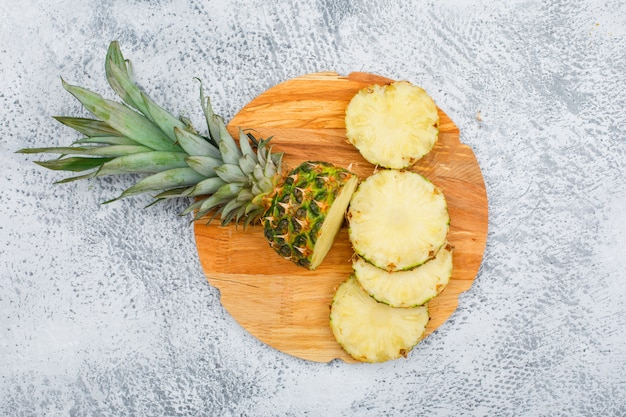 Yummy pineapple slices in a round chopping board on grunge surface, top view.