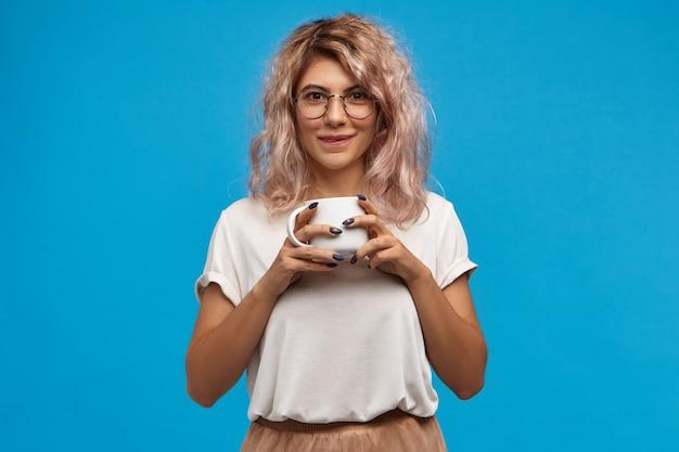 おいしい。甘いホットチョコレートを楽しんで丸い眼鏡をかけてかわいいオタクの若い女性の肖像画。白いマグカップを保持し、おいしい淹れたてのコーヒーを飲むピンクがかった髪のかわいい女の子