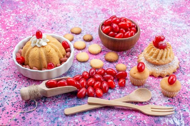 Вкусный простой торт со сливками и свежим арахисом, печенье из красного кизила на ярко-фиолетовом столе, бисквитный торт, сладкий орех и ягода