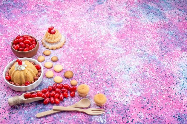 Вкусный простой торт со сливками и свежим арахисом, красный кизил на ярком светлом столе, бисквитный торт, сладкий орех и ягода