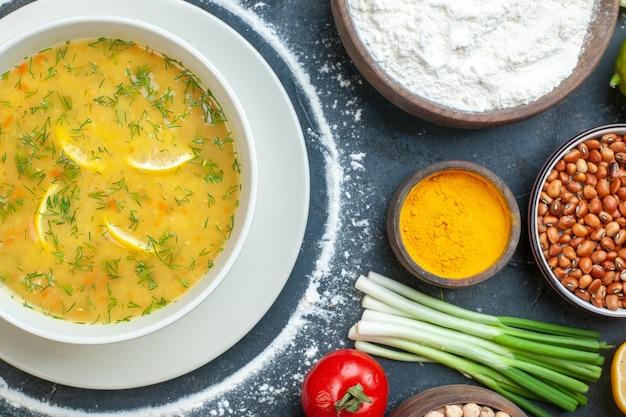 Zuppa gustosa servita con limone e verde in una ciotola bianca e farina di pomodoro olio bottiglia farina verde fasci uova