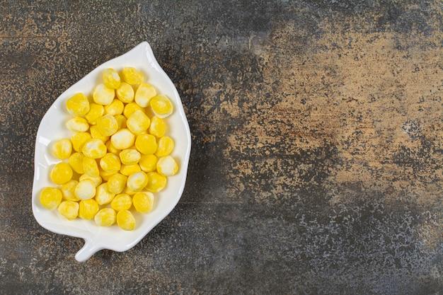 葉の形をしたプレートにおいしい黄色いキャンディー。