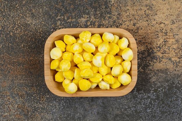 Yummy caramelle gialle sul piatto di legno.