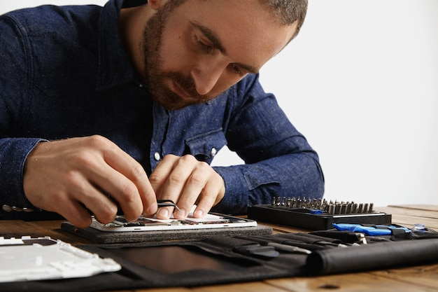 Yung bearded master looks inside disassembled electronic device while repairing it with tools