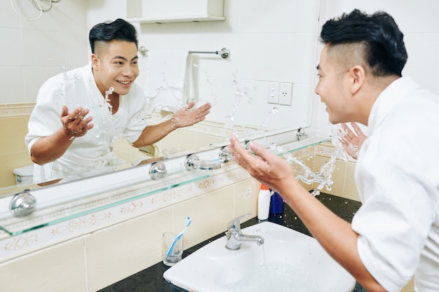 Yuong man splashing water in sink