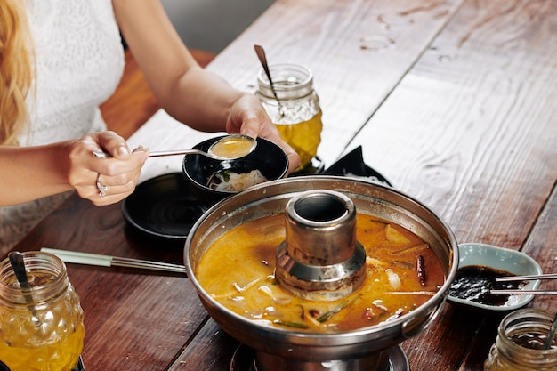 Yuong woman eating delicious squid soup