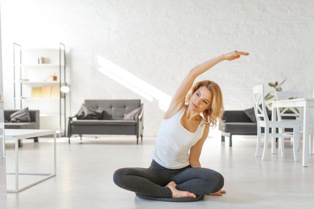 Юонг женщина сидит на полу в позе йоги