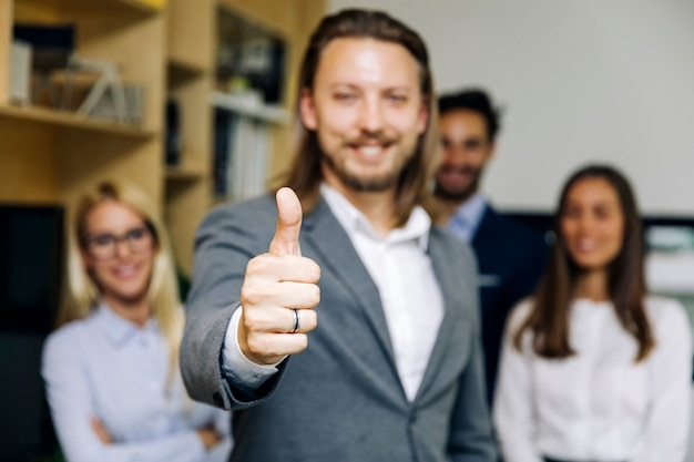 Yuoung businessman with thumb up standing in the office
