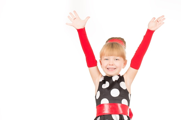 Яппи! портрет маленькой девочки в ретро-платье, радостно кричащей с поднятыми вверх руками