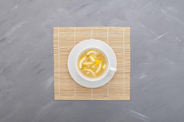 灰色の背景に白いカップのゆず茶またはユジャ茶人気のあるアジアのシトロンティー上面図