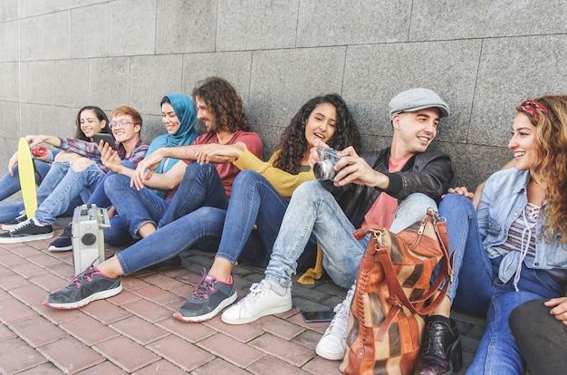 Молодые друзья тысячелетия, весело болтающие, фотографирующие со старинной камерой и использующие смартфоны - молодежь, поколение z, технологические тренды и многорасовая концепция - главное внимание на правильном лице парня