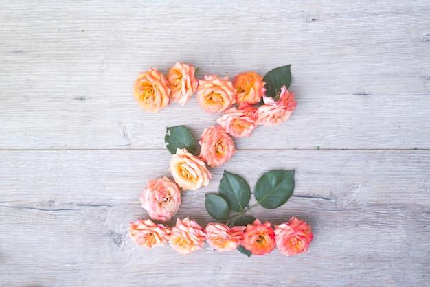 Z、灰色の花のアルファベットは、灰色の木製の背景に、フラットなレイアウト