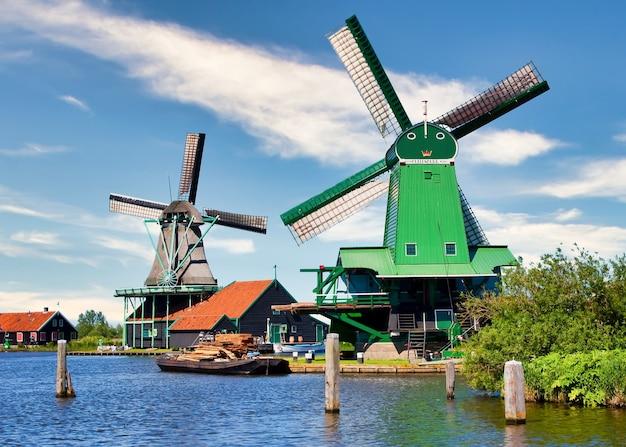 Zaanse schans, netherlands - 2020년 8월경: 푸른 하늘과 강물이 있는 암스테르담에 가까운 녹색 시골에 있는 네덜란드 풍차.