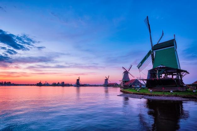 Ветряные мельницы на известном туристическом сайте zaanse schans в голландии с драматическим небом. зандам, нидерланды