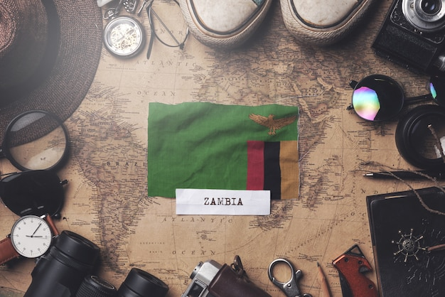 Zambia flag between traveler's accessories on old vintage map. overhead shot