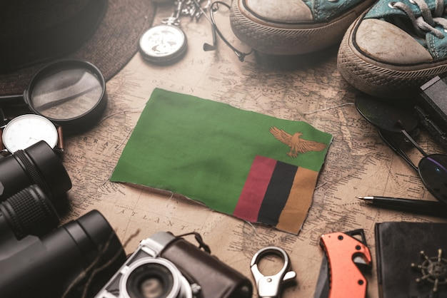 Zambia flag between traveler's accessories on old vintage map. tourist destination concept.