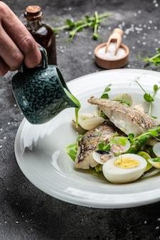 Филе судака с морепродуктами и овощами. повар поливает блюдо сливочным соусом