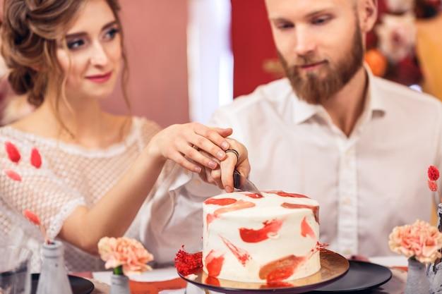 Zaporizhia, ukraine - december 15, 2019: newlyweds cut wedding cake while in beautiful interior.