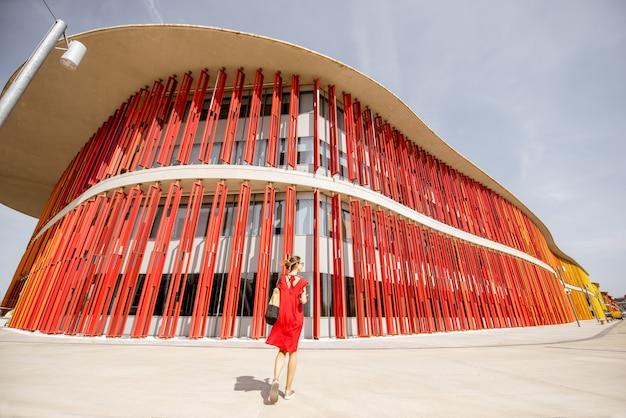 Zaragoza, spain - august 21, 2017: woman in red dress walking near the modern building pavilion of expo 2008, international exposition held in zaragoza, spain