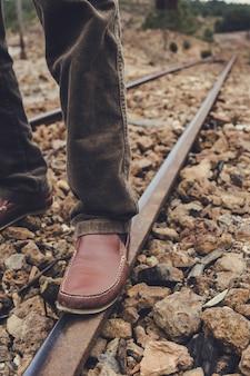 Zarandaの古い駅の小石の床の上の列車トラックのレールの上の足