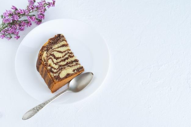 Торт зебры на белой поверхности. кусок бисквитного торта на белой тарелке. скопируйте пространство. вид сверху.