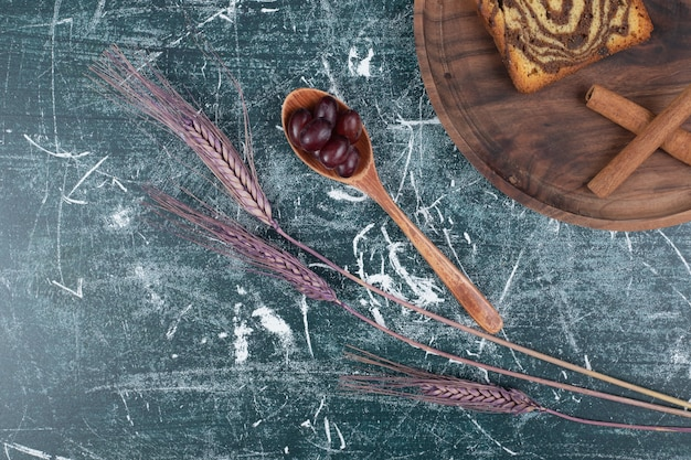 Torta zebra sul piatto di legno con cannella e uva. foto di alta qualità
