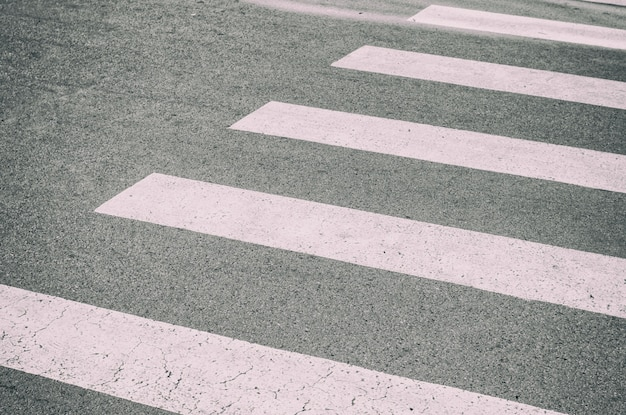 Zebra crossing painted on the asphalt, detail of a signal circulation, traffic information for pedestrians and drivers, security in concrete jungle concept