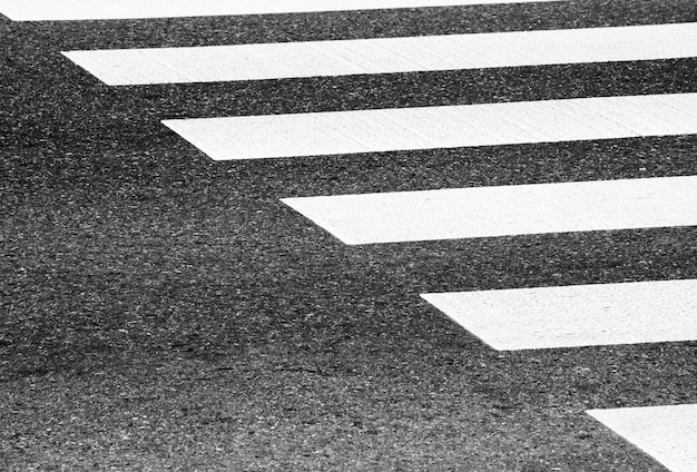 Zebra crosswalk on a asphalt road - closeup background