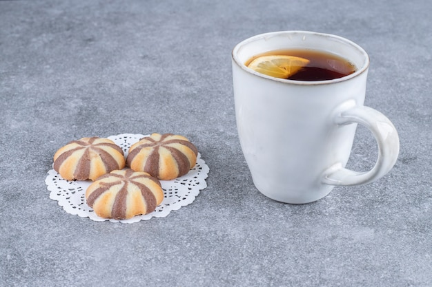 Zebra pattern biscuits and cup of tea on marble surface