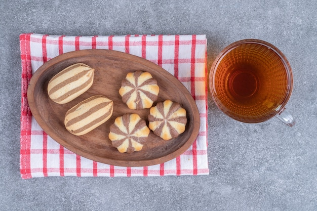 Zebra pattern biscuits on wooden plate with cup of tea