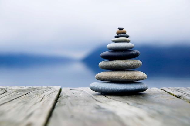 Ciottoli in equilibrio zen accanto a un lago nebbioso