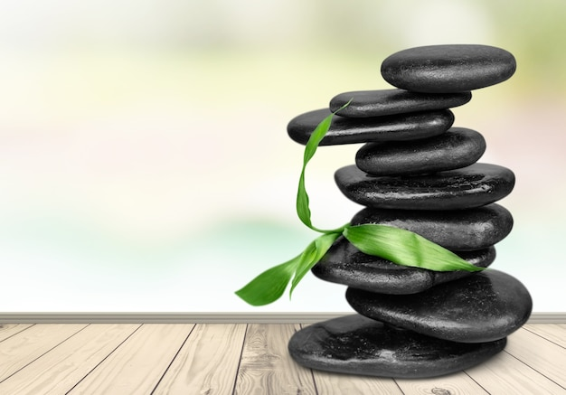 Zen basalt stones and leaves on background