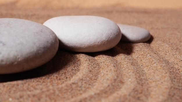 Дзен-сад. пирамиды из белых и серых дзен-камней на белом песке с абстрактными волновыми рисунками.